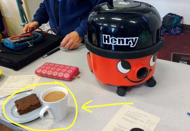 Henry vacuum cleaner getting some TLC - this picture also points out a cup of tea and brownie - did I mention that volunteers get a token for one cup of tea and cake for FREE?!?